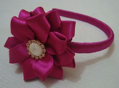 Tiara revestida em fita cetim com flor e detalhes de strass com botão chaton.
