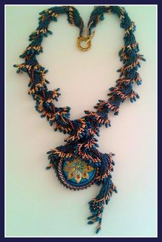 Midnight Blue necklace designed by Angelika Motzkin. In this design Angelika wrapped a Czech glass cabachon with Japanese seed beads and trimmed with Rizo beads.