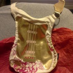 HANNAH MONTANA GUITAR  PURSE A Disney product made of soft canvas with gold metallic material and four red rhinestones...red and gold floral pattern. Open body inside zips closed on top. New used once...Shaped like a guitar. Hannah Montana  by Disney Bags