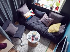 An aerial view of a teen room lounge area with a day-bed sofa, an easy chair and a bedside table