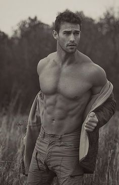 Model Jay Byars sexily removes his shirt in the middle of a field at sunset. (Thank you!)