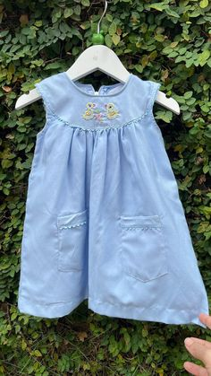 This blue coloured cotton dress has handy twin pockets on the side of the dress complete with hand embroidered ducks on the yoke giving this sleeveless dress a classy nature lover look. The ric rac edging in matching colors ont eh dress and pockets adds an elegant look to the dress. An evening party wear would be the excellent choice to wear this dress. 6 Month Old Baby, Matching Colors, Baby Shop, Evening Party, Little Babies, Ducks, Cotton Dresses, Party Wear, Twin