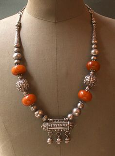 """A traditional Yemen necklace, with the large, hallmaked silver beads and  amulet holder with tassels made by a Jewish silversmith, and a set of four antique """"amber"""" beads of European manufacture.  