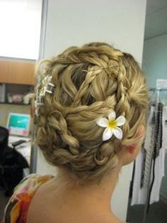 Really pretty braided updo, but I don't understand why they ruined it with bobby pins and plastic flowers!