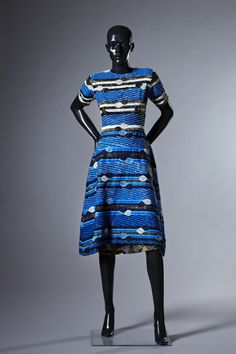 A dress by Jewel By Lisa. Blue dress with beading. Overall blue colour but with horizontal stripes and circles of blue, black, white and gold/yellow beads.  Displayed at the exhibition Fashion Cities Africa, Brighton Museum & Art Gallery April 2016-January 2017.  Professional images of outfits, clothes and accessories, mostly arranged in their original 'looks' from Fashion Cities Africa exhibition, 2016-2017, taken by Tessa Hallmann on our behalf.