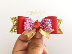 Disney Princess Eleanor of Avalor Red Pink and Gold Hair Bow  This piece is inspired by the new Disney Princess Eleanor of Avalor. If you would like colors substituted, please message me. Approx. 3 1/2 wide  Layers of Beautiful hand cut chunky glitter fabric hand lined with felt for comfort and design, topped with Redgenuine leather topped with glitter mini loop, gold metallic leather peaks and finished with a red rhinestone Gem Center.   Please choose from the wide array of options of…