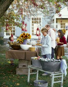 I love the look of this back yard party.  The hanging lanterns from the tree, the stacked crates at the base of the burlap covered table and the old wash tubs filled with drinks and apples.