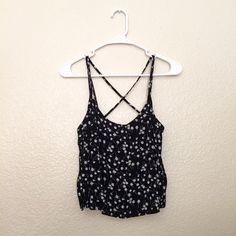Black Flowy Top Black flowy top with white flowers and criss cross back. Only worn once. Tops Tank Tops