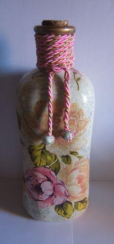 Botella en tonos rosas con motivos florales.