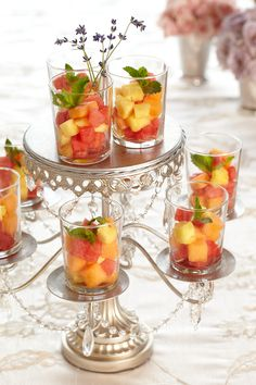 Fruit Salad. Give dramatic flourish to a simple staple at the baby shower by displaying grapefruit, melon and strawberries with mint atop a classical candelabra. #APerfectEvent #DebiLilly #Babyshower #BabyShowerTrends