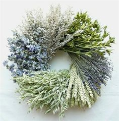 """Soft blue and green tones make this dried floral wreath easy to incorporate into your home decor. Measuring 22"""" in diameter, the wreath features a stunning combination of artemesia, nigella orientalis, Munstead lavender, beardless wheat, green avena, and blue larkspur"""