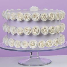 Rows of Roses Cake - The ribbon roses featured in our Decorating Basics course have all the excitement and detail any cake needs. This cake is the perfect opportunity to practice them as dozens of pretty white flowers encircle a pretty violet-iced cake.