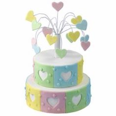 Pre-made gum paste decorations seem to burst from the center of the Hearts Fireworks cake. Matching pastel fondant panels with cut-out heart centers wrap around the cake sides to add dimension.