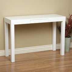 @Overstock.com - Lachlan Glossy White Sofa Table - Accent your living area or hallway with this white wooden sofa table featuring a single drawer for storage. The glossy white finish will blend with virtually any d�cor for a classic, elegant look thats perfect for stashing keys or remotes out of sight.  http://www.overstock.com/Home-Garden/Lachlan-Glossy-White-Sofa-Table/4850189/product.html?CID=214117 $125.99
