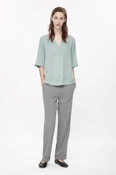 An A-line style, this top has wide half sleeves and a deep, crossover v-neckline. With a folded pleat along the front, it is made from lightly textured fabric that has loose, fluid quality.