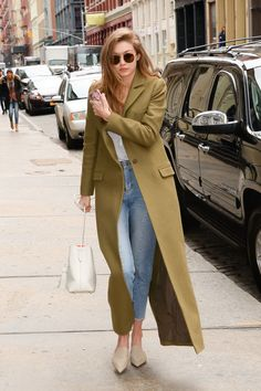 Gigi Hadid in a floor-length olive green coat, white tee, high-waisted jeans, pointed-toe flats, white Mansur Gavriel bucket bag and round sunglasses.
