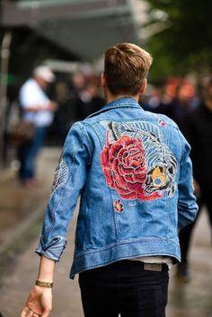 As jaquetas jeans estão super em alta e podem ser encontradas em vários shapes, lavagens e detalhes. Na foto: jaqueta jeans clara com bordados nas costas e calça escura.