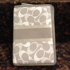 A silver and grey Coach wallet This is an awesome wallet to have to stick in your pocket or to keep bulk down. There is an imperfection on the front as well as some wear marks on the edges. Still looks great though and is in great condition Coach Bags Wallets
