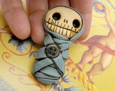 Adorable baby mummy bandaged in grey. Creepy and cute. Lovely and primitive. Brooch, keychain or pendant (you choose)