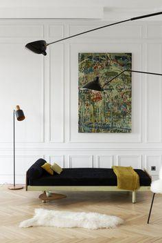 Chez lounge with unframed art, herringbone wood floors, and modern lighting.