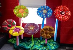 We used the plastic  chip/dip trays from the Dollar Tree and spray painted them . Once the paint dried you can decorate them however you like! They are being held up with a plunger. We put either a pool noodle or a plastic sound maker over the plunger for the stem. This project was inexpensive and makes for an awesome decoration!