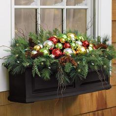 Christmas window box - shiny ball ornaments resting on a bed of evergreen boughs and pinecones.