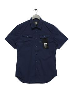 After a big year for the Dutch denim brand G-Star are back for 2017 with one of their best collections to date. The 3301 short sleeve shirt is a standout item showcasing the best of the brand. A modern twist on a classic workwear design the shirt is cut from a comfortable cotton elastane blend in a more contemporary slim fit. The bold Police blue colourway features subtle detailing including a branded G-Star patch to the chest. - 98% Cotton, 2% Elastane- Police Blue- Point collar - Curved…