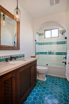 House of Turquoise: Erin Hedrick Design.  Beach cottage bathroom with pretty turquoise and white tiles and arch above bathtub.