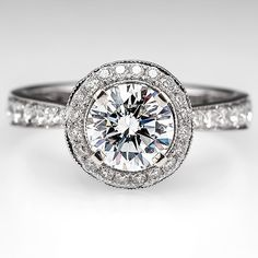 This 1.15 carat captivating sparkler is in a diamond halo setting with a high profile. The band is adorned with even more diamonds.