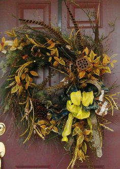 Wreath with fall colors: gold, browns, orange, blues. Also feathers, pods, leaves, twigs, zebra grass and funky ribbons.
