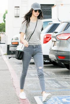 Kendall Jenner wears a gray top with gray jeans, white sneakers and a baseball cap.