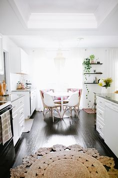 A bright, white kitchen with a touch of green seedlings adds the perfect touch of color to a bare living space.