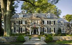 a stacked stone Georgian revival style home in Moorestown, New Jersey, complete with matching retaining walls. Gorgeous 12-over-12 windows dressed with black shutters, third floor dormers, matching black door with sidelights and fanlight surrounded by classical style portico, and a lovely winding wing off to the right. via Foo Dog