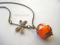 A brass dragonfly connects to a large 16mm fire agate stone that is enveloped with antique copper filigree caps. The stone hangs from an antique brass chain that measures 16 inches and closes with a lobster clasp. The single dragonfly adds a pleasant sense of asymmetry to this necklace. (length of chain may be adjusted upon request)  Check my shop for the original dragonfly necklace in turquoise.  A serene piece for nature lovers!  Please note that the exact stone pictured has sold. The…