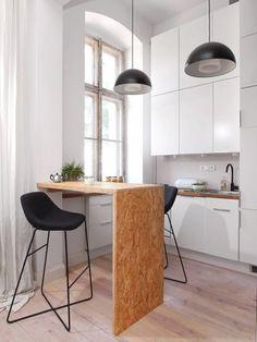Aneks kuchenny można przygotować na barku z płyty OSB, który służy przede wszystkim jako stół jadalny. Ściana pokryta farbą tablicową pełni funkcję domowego słupa ogłoszeniowego.