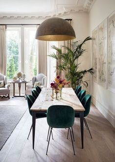 Rustic, minimal, and modern dining room  with unique features like the lamp, and suede green chairs, wood table, and big, beautiful plants