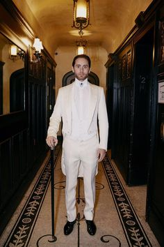 Heading to the Met Gala, Jared Leto in a custom Gucci white satin peak lapel tailcoat with white pique cotton gilet, white evening shirt, a crystal brooch and a hand carved black lacquer cane with silver and crystal embellished cat head detail by Alessandro Michele.