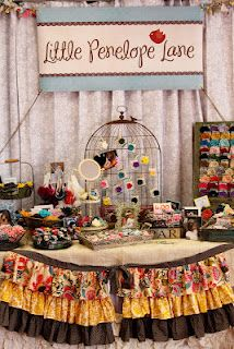 Little Penelope Lane Booth - I love the bird cage display and the ruffles on the table