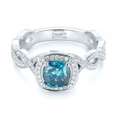 This dazzling engagement ring features a cushion cut blue diamond in the center, surrounded by a halo of bright cut set white diamonds, and accented by additional bright. Design Your Own Engagement Rings, Round Diamond Engagement Rings, Beautiful Engagement Rings, Diamond Rings, Alternative Engagement Rings, Ring Verlobung, Princess Cut Diamonds, White Diamonds, Cushion Cut
