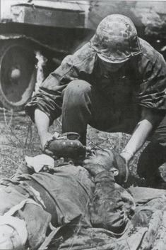 Waffen SS trooper offers water to mortally wounded Soviet tank crew member, 1943.