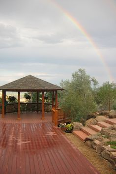 The rainbow ends at this rain-soaked patio and gazebo, highlighting the colors and textures of the patio. By Native Edge Landscapes in Boulder, Colorado.