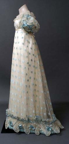 Evening dress of silk gauze with a woven pattern of blue leaves in flossed silk, trimmed with silk net and blue satin. c1821