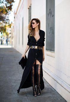 Robe longue noire, déboutonnée aux jambes et au décolleté, lunettes de soleil, cuissardes à lacets, pochette noire