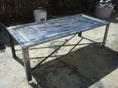 Custom built steel coffee table with 2″ solid steel angle iron legs and polished antique lavatory stall door tops.  Great piece of repurposed industrial furniture.
