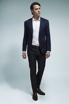 Camisa branca com micropadronagem suave e vista azul contrastante, blazer marinho, calça jeans com lavagem escura e mocassim e cinto de couro marrom para finalizar. Deixar parte do tornozelo à mostra torna o look mais contemporâneo.