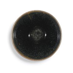 'JIAN' 'HARE'S FUR' TEA BOWL, SONG DYNASTY, heavily potted standing on a low foot, the deep conical body rising to a shallow concave groove around the exterior of the mouth, applied in a lustrous bluish-black glaze with streaks of brown radiating from the waisted mouth, the dark glaze with unusual flecks of copper-coloured shimmer, the glaze stopping irregularly above the foot, 12 cm | sotheby's