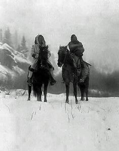 Two Crow (Apsaroke) Indian men on Horseback in Wintertime. Photo by Edward S. Curtis, 1908. (B&W copy)