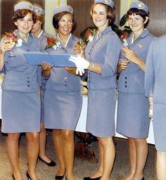 Assistentes de bordo da Pan Am, com os seus uniformes impecáveis, mais outra imagem para apelar ao glamour da viagem. Usavam conjuntos saia (pelo joelho) casaco azuis, a combinar com o chapéu, luvas e camisa brancas.