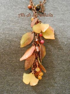 """Ali di Libellula: SHRINK PLASTIC -- """"Leaves, in different colours and shapes, are made of shrink plastic, and hang from a copper chain interspersed by a vaiety of hardstones: tiger's eye, cornaline, agate. The toggle-bar clasp is on the front of the necklace""""    Notice the gingko leaf!"""