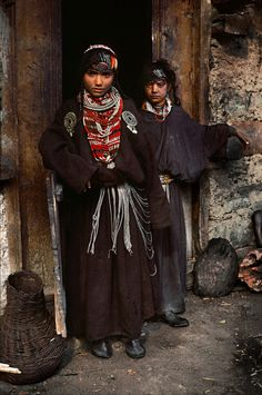 kpk-fata: Khyber Pakhtunkhwa Two Kalash girls standing by a doorway. Chitral district, 1981. Photograph by Steve McCurry.